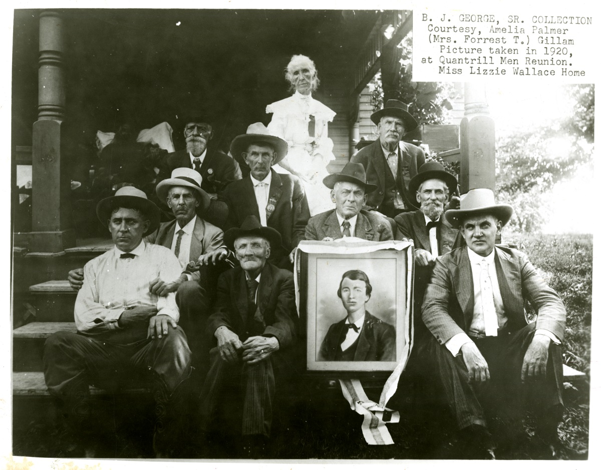 "Attendees of the 1920 reunion at Wallace Grove with a picture of a young Quantrill. A special guest was Jesse James Jr. (front right), son of the famous outlaw.  Lizzie ""Aunt E"" Wallace is back-row center."