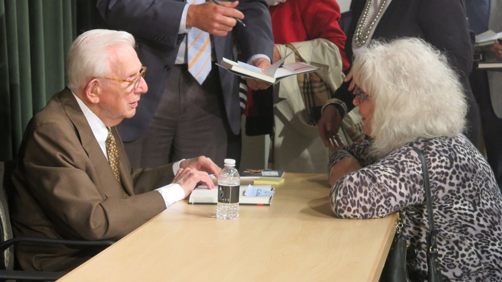 Henry Bloch signs books and visits with event attendees.