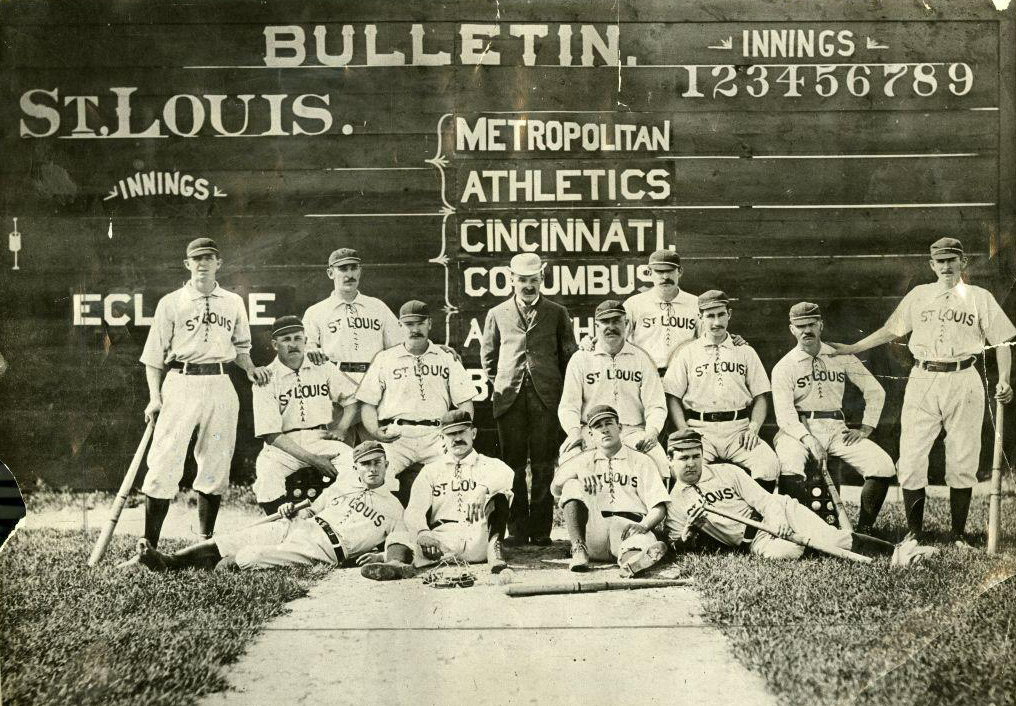 Black and white photo of The 1883 St. Louis Browns standing in front of a wooden score board.