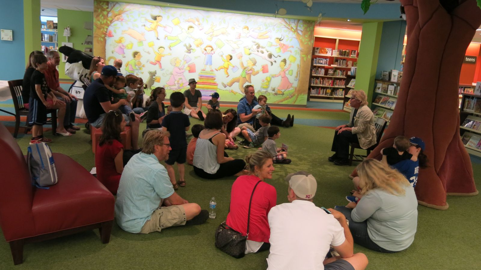 Image of the children's area at the Central Library with people sitting together for storytime.