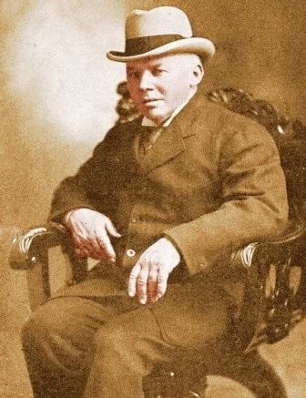 Photograph portrait of a man in a suit and a hat seated in a chair.