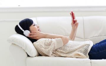 Image - woman on couch listening to audiobook