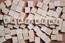 """wooden tiles from the game scrabble spelling out """"fake news"""""""
